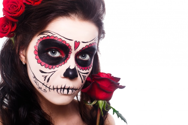 Young woman in day of the dead mask skull face art and rose