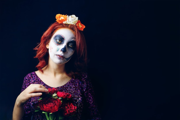 A young woman in day of the dead mask skull face art