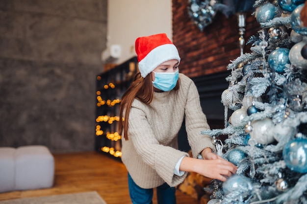 A young woman decorates the christmas tree in medical masks