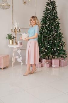 젊은 여자는 흰색과 금색의 크리스마스 장난감 클래식 인테리어로 크리스마스 트리를 장식