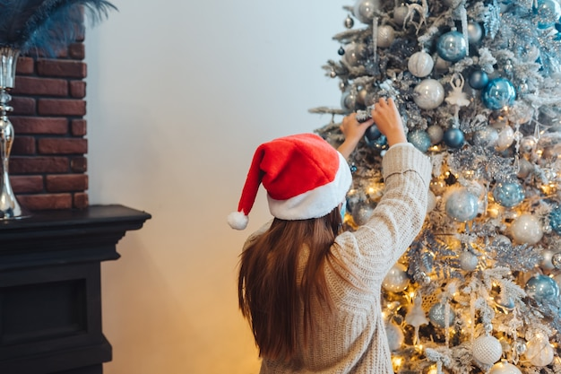 Una giovane donna decora l'albero di natale