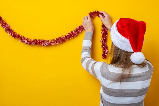 젊은 여자는 노란색 배경에 빨간 크리스마스 반짝이로 장식합니다.