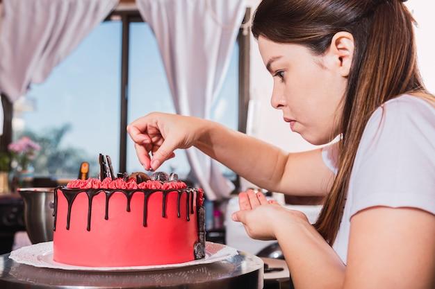 Молодая женщина украшает вкусный торт шоколадом на кухне.