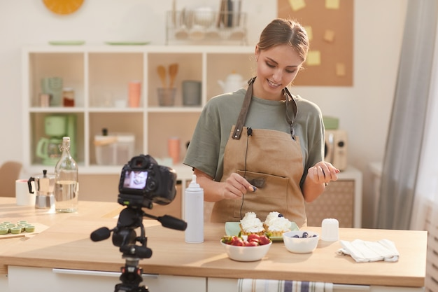 台所のテーブルに立って、ブログのためにカメラに見せながら、ベリーでケーキを飾る若い女性