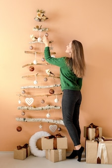 家でクリスマスツリーを飾る若い女性