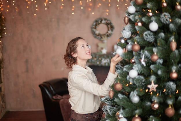 彼女のリビングルームでクリスマスツリーを飾る若い女性。