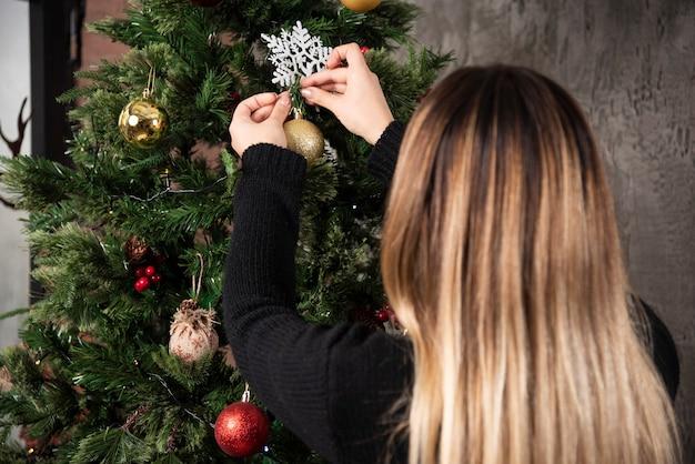 Giovane donna che decora l'albero di natale e si prepara per le vacanze. foto di alta qualità