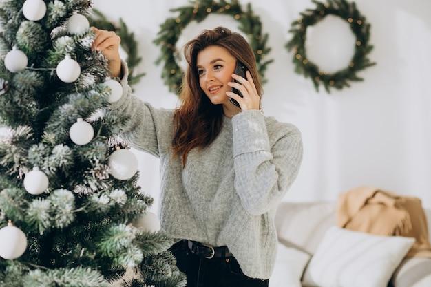 Giovane donna che decora l'albero di natale