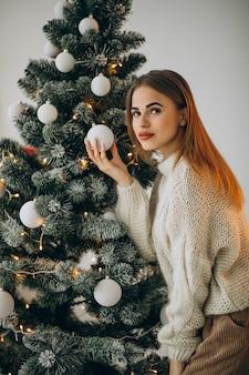 Молодая женщина украшает елку
