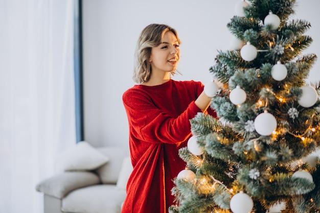 크리스마스 트리를 장식하는 젊은 여자