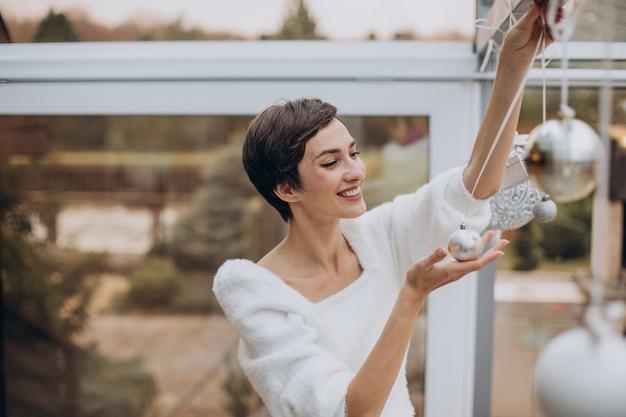 Молодая женщина украшает дом елочными игрушками