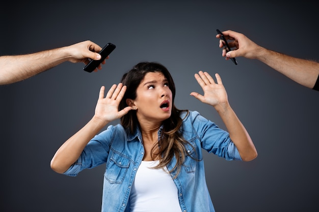 Young woman defending herself against phones. she is tired of phone conversation.