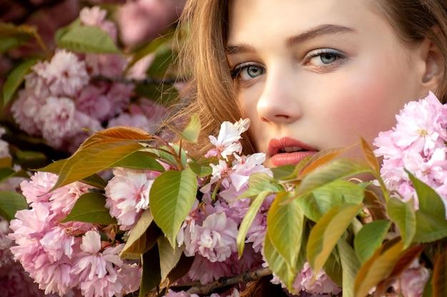 若い女性の繊細な桜の木の花カメラをのぞき込む