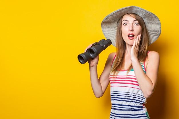 Молодая женщина восхитительно удивила шляпу и полосатое платье, держа бинокль на желтом пространстве