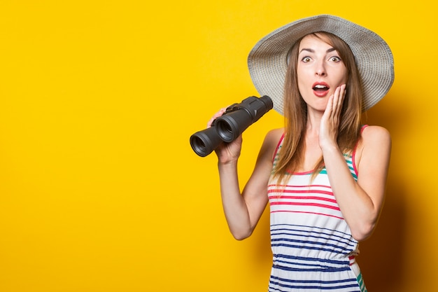 Young woman delightfully surprised hat and striped dress holding a pair of binoculars on a yellow space
