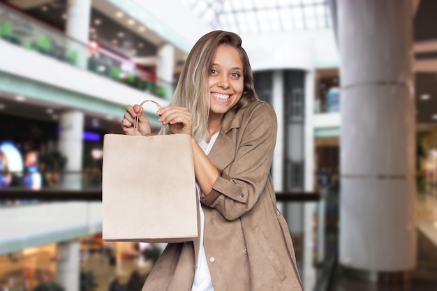 A young woman demonstrates paper eco bag with copy space for the logo on a blurry background of mall