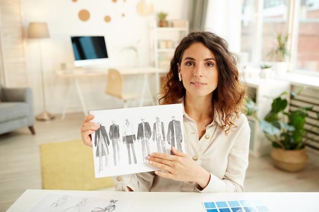 옷 디자인 스케치를 보여주는 젊은 여자