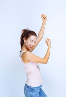 彼女の腕の筋肉、縦断ビューを示す若い女性