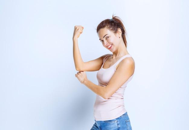 Молодая женщина демонстрирует мышцы рук, вид профиля