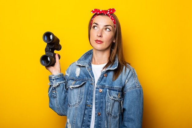 Young woman in a denim jacket and a raft on her head looks up and holds binoculars in her hands on a yellow wall.
