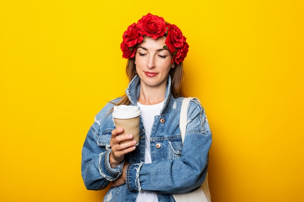 Young woman in a denim jacket and a wreath of red flowers on her head holds a paper cup with coffee and looks at it on a yellow wall.