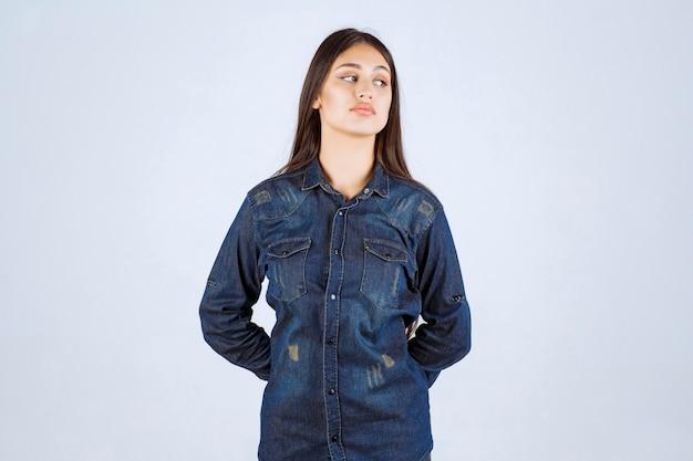 Giovane donna in camicia di jeans che dà pose neutre senza reazioni