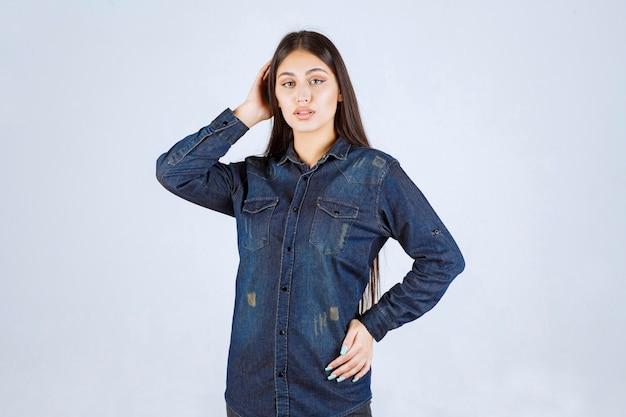 Giovane donna in camicia di jeans che dà pose neutre e seducenti senza reazioni