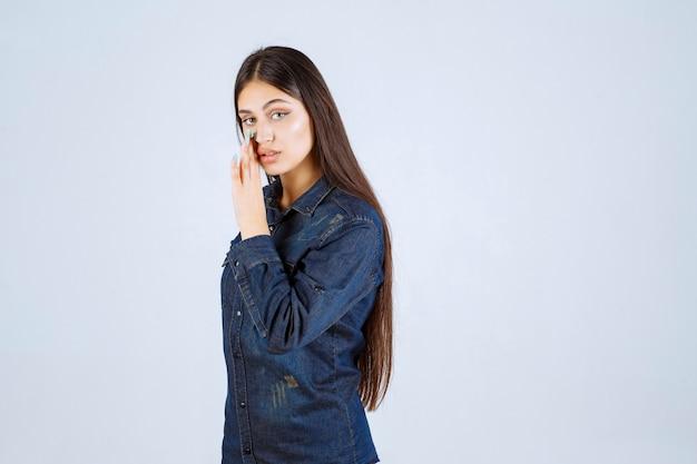 Giovane donna in camicia di jeans spettegolare e parlare segreto