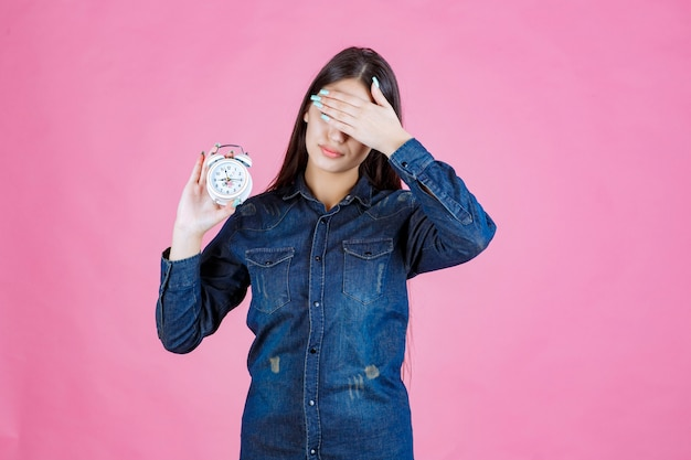 Young woman in denim shirt holding the alarm clock and covering her eyes