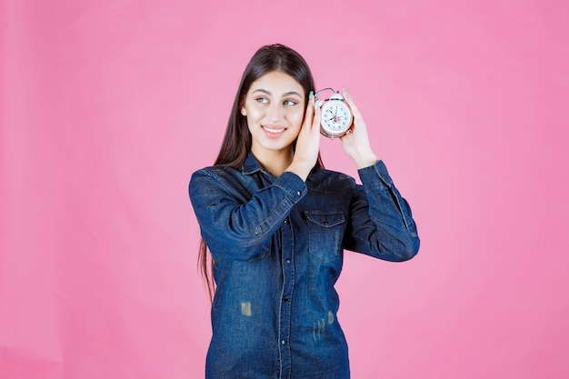 Young woman in denim shirt holding the alarm clock to her ear and listening
