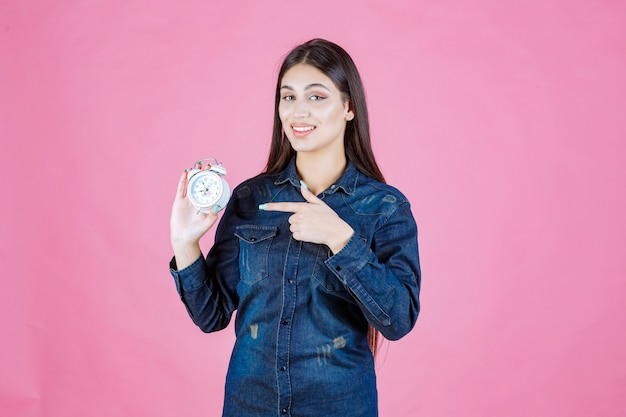 Young woman in denim shirt holding the alarm clock and pointing at it