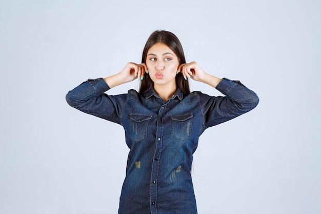 Giovane donna in camicia di jeans che tiene le sue orecchie