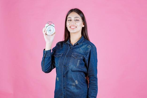 Giovane donna in camicia di jeans che tiene e promuove una sveglia