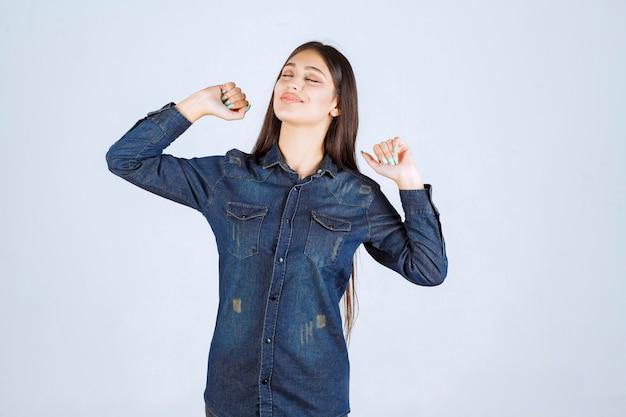 La giovane donna in camicia di jeans sembra esausta e assonnata