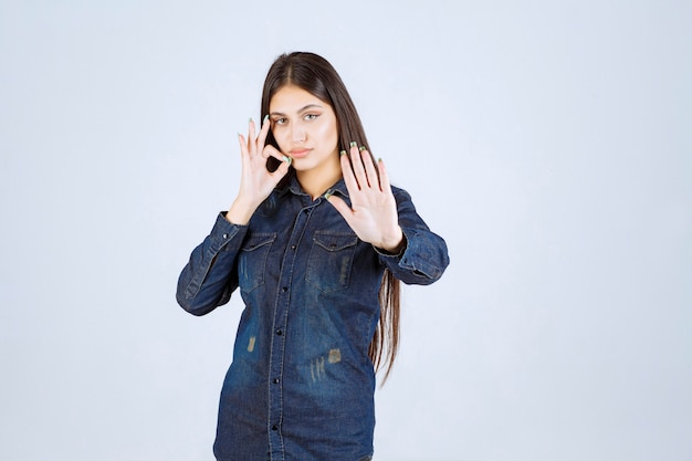Giovane donna in camicia di jeans che punta alla bocca e chiede di tacere