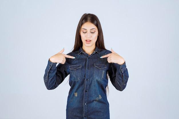 Giovane donna in camicia di jeans che punta a se stessa