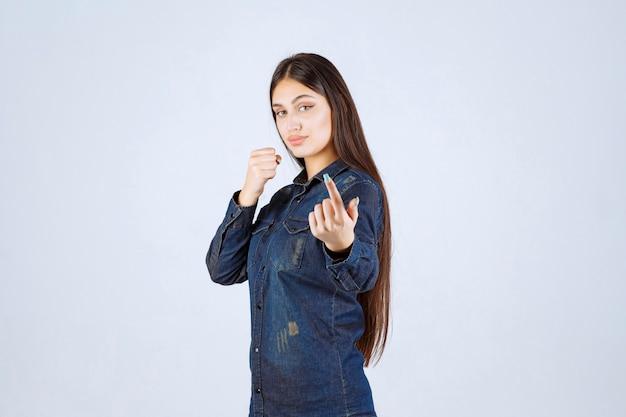 Giovane donna in camicia di jeans che punta alla persona di fronte a lei