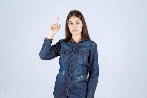Giovane donna in camicia di jeans che punta a qualcosa al rialzo