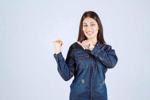 Giovane donna in camicia di jeans che punta a qualcosa dietro