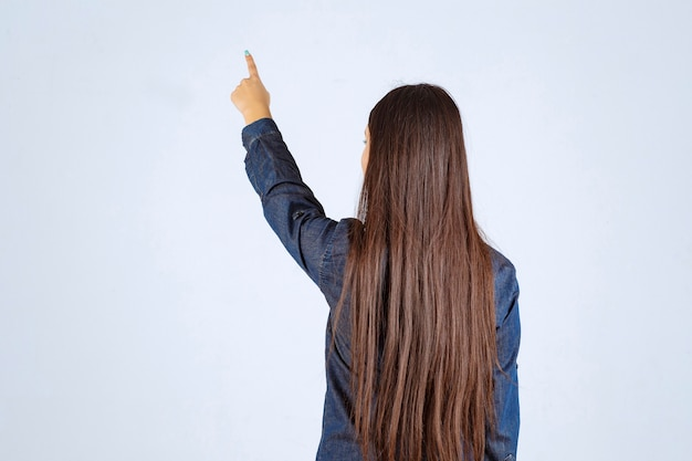 Young woman in denim shirt pointing at something behind