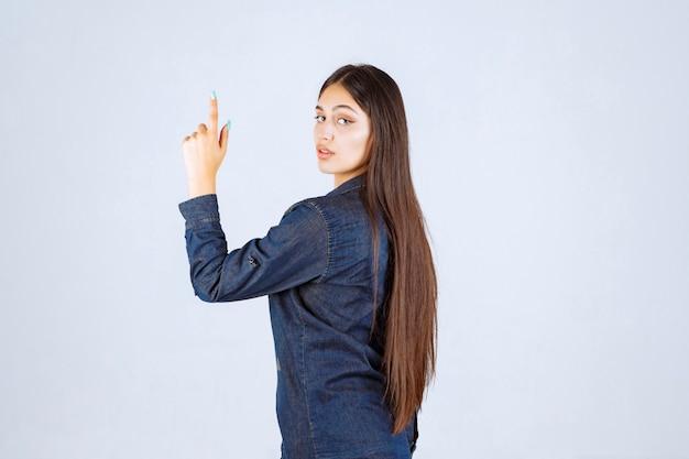 Giovane donna in camicia di jeans alzando le mani e indicando qualcosa di cui sopra