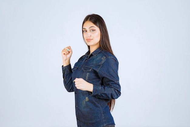 Young woman in denim shirt running from the place