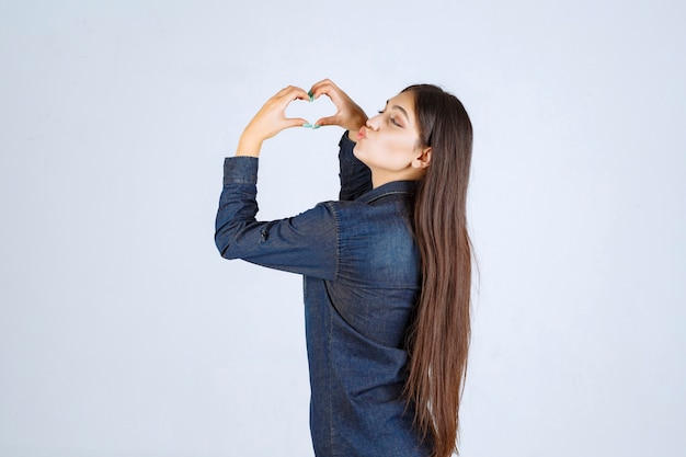 Young woman in denim shirt sending love
