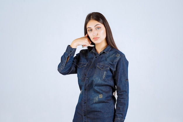Giovane donna in camicia di jeans che mostra il segnale di chiamata
