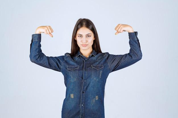 Giovane donna in camicia di jeans che mostra i suoi muscoli del braccio
