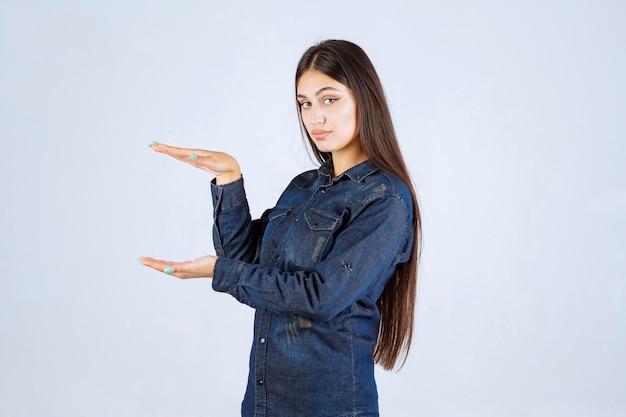 Giovane donna in camicia di jeans che mostra le misure di un prodotto