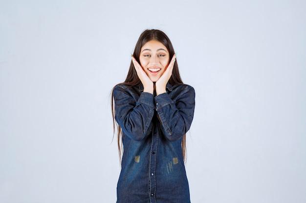 Giovane donna in camicia di jeans sorridendo e facendo bel viso
