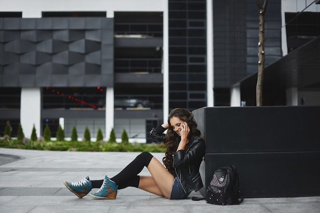 A young woman in denim shorts and leather jacket talking by phone and sitting on the street of a european city on a summer day