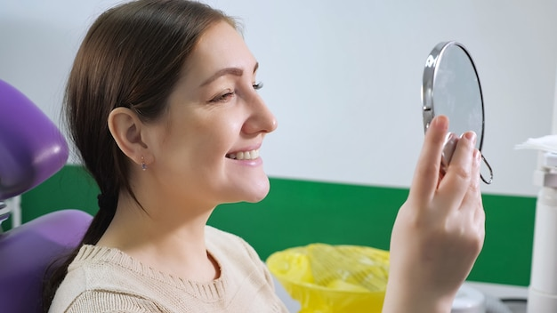 Young woman in dental chair examines her teeth in the mirror after treatment, side view. teeth care concept.