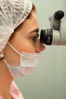 Young woman dentist doctor looks through a professional microscope in a dental clinic